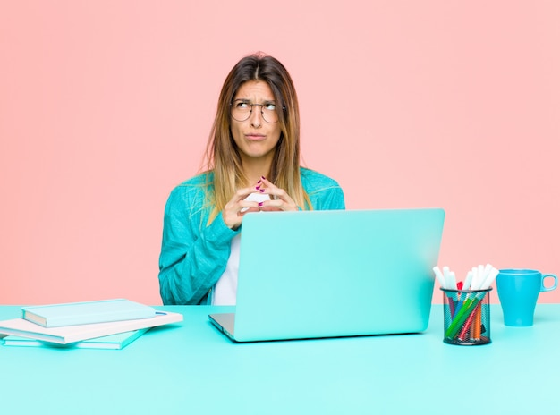 Młoda ładna kobieta pracująca z laptopem knująca i konspirująca, myśląca o podstępnych sztuczkach i oszustwach, przebiegła i zdradzająca