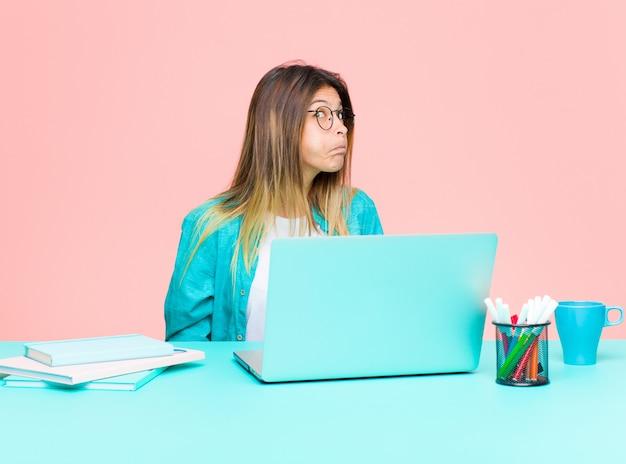 Młoda ładna kobieta pracująca z laptopem o głupkowatym, szalonym, zdziwionym wyrazie, nadymający się policzki, uczucie wypchania, tłuszczu i jedzenia