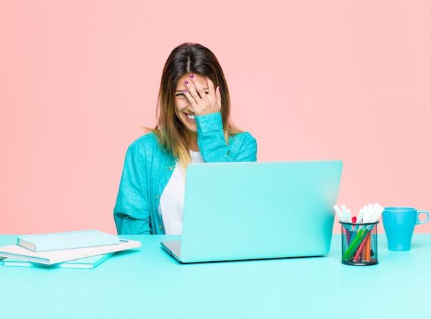 """Młoda ładna kobieta pracująca z laptopem, śmiejąca się i uderzająca w czoło, jak mówiąc: """"och!""""! zapomniałem lub to był głupi błąd"""