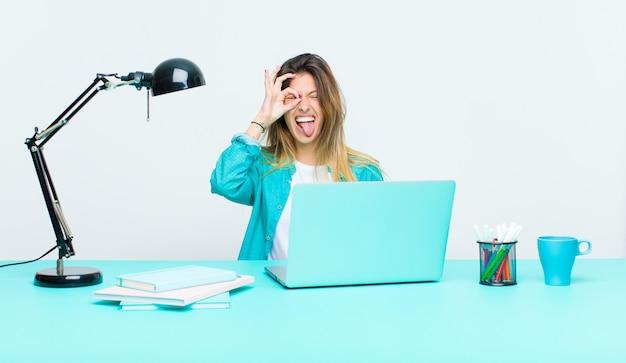 Młoda ładna kobieta pracująca z laptopem, uśmiechając się radośnie ze śmieszną twarzą, żartując i patrząc przez wizjer, szpiegując tajemnice