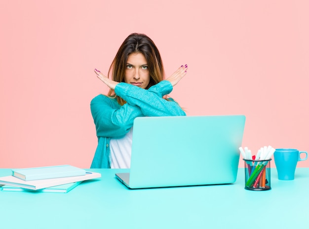 Młoda ładna kobieta pracująca z laptopem wygląda na zirytowaną i dość twojej postawy, mówiąc wystarczająco dużo! ręce skrzyżowane z przodu, każąc ci przestać