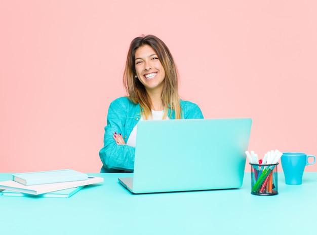 Młoda ładna kobieta pracująca z laptopem, wyglądająca jak szczęśliwy, dumny i zadowolony wykonawca, uśmiechając się z założonymi rękami
