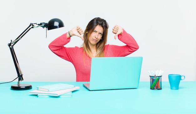 Młoda ładna kobieta pracująca z laptopem, wyglądająca na smutną, rozczarowaną lub wściekłą, pokazująca kciuk w nieporozumieniu, czująca się sfrustrowana
