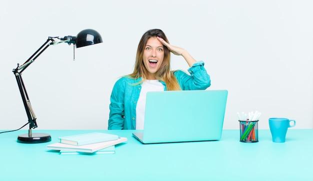 Młoda ładna kobieta pracująca z laptopem, wyglądająca na szczęśliwą, zdziwioną i zaskoczoną, uśmiechniętą i zdającą sobie sprawę z niesamowitych i niesamowitych dobrych wiadomości