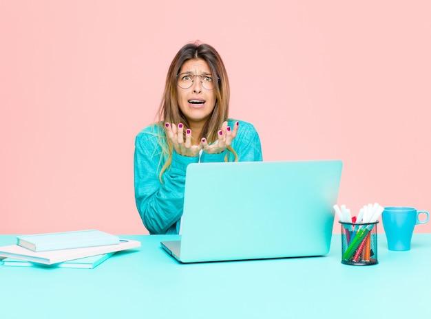 Młoda ładna kobieta pracująca z laptopem wyglądająca na zdesperowaną i sfrustrowaną, zestresowaną, nieszczęśliwą i zirytowaną, krzyczącą i krzyczącą