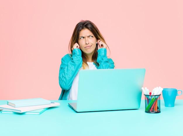 Młoda ładna kobieta pracująca z laptopem, wyglądająca na złą, zestresowaną i zirytowaną, obejmującą uszy ogłuszającym hałasem, dźwiękiem lub głośną muzyką