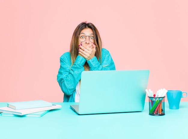 Młoda ładna kobieta pracująca z laptopem zakrywającym usta dłońmi z zszokowanym, zdziwionym wyrazem, trzymająca w tajemnicy ups