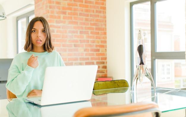 Młoda ładna kobieta pracująca, zszokowana i zaskoczona z szeroko otwartymi ustami, wskazująca na siebie