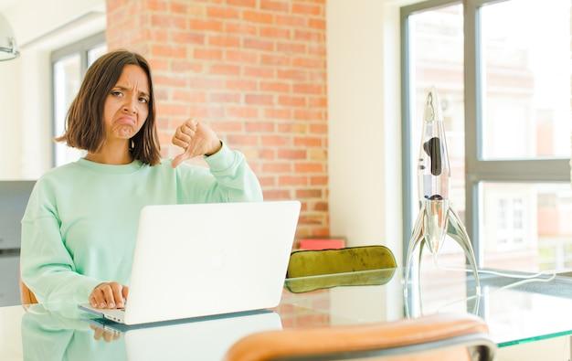 Młoda ładna kobieta pracuje, czuje się zła, zła, zirytowana, rozczarowana lub niezadowolona, pokazuje kciuki w dół z poważnym spojrzeniem