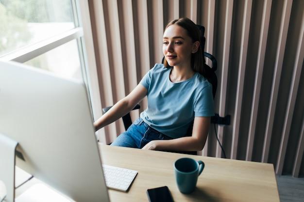 Młoda ładna kobieta pracuje na komputerze w domowym biurze