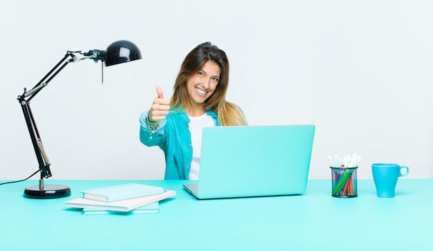 Młoda ładna kobieta pracuje z laptopem czuje się dumny, beztroski, pewny siebie i szczęśliwy, uśmiechając się pozytywnie z kciuki do góry