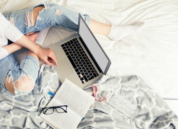 Młoda ładna kobieta pracuje z laptopem na łóżku