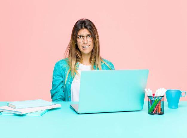 Młoda ładna kobieta pracuje z laptopem patrzeje zdziwiony i zmieszany