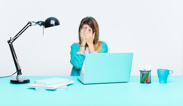Młoda ładna kobieta pracuje z laptopem zakrywającą twarz rękami, zerkając między palcami z zaskoczonym wyrazem twarzy i patrząc w bok