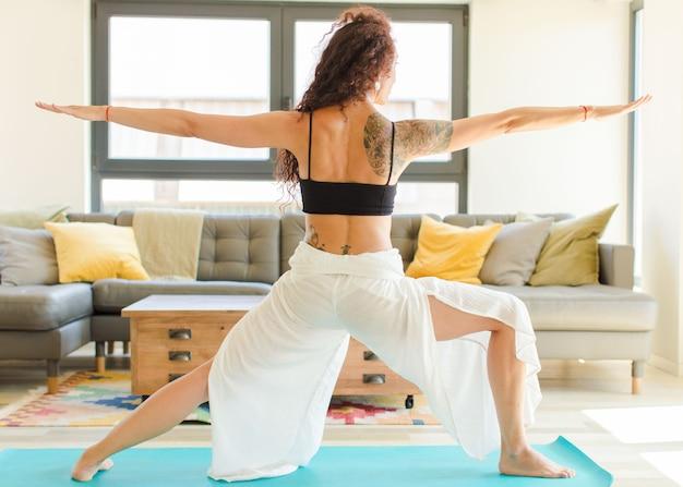 Młoda ładna kobieta praktykuje jogę w pomieszczeniach. relaks i trening w domu