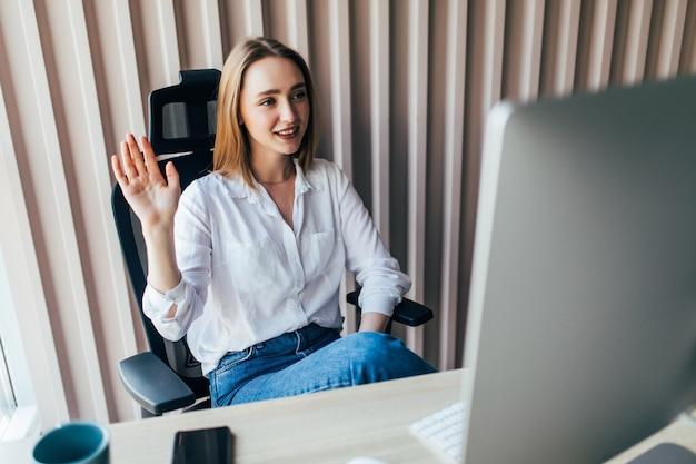 Młoda ładna kobieta prowadzi rozmowę wideo przez laptopa w biurze