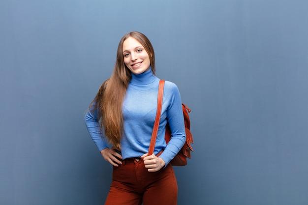 Młoda ładna kobieta przeciw błękit ścianie z odbitkową przestrzenią