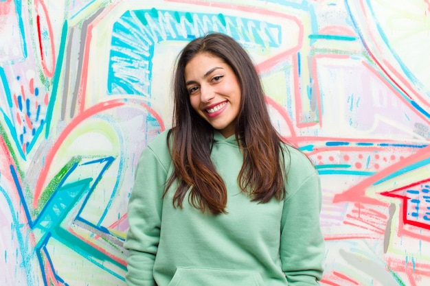 Młoda ładna kobieta przeciw graffiti ścianie