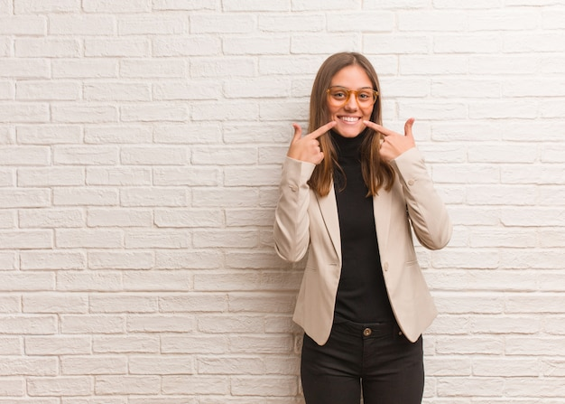 Młoda ładna kobieta przedsiębiorca uśmiecha się, wskazując usta
