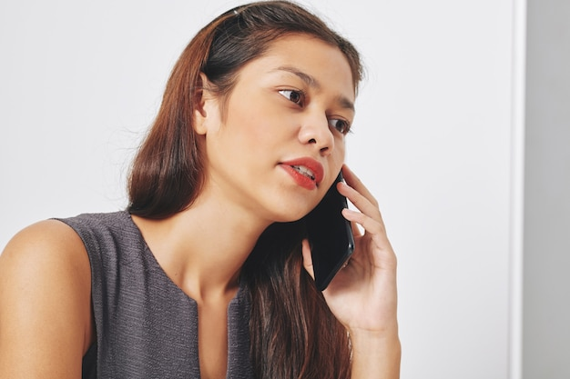 Młoda, ładna kobieta przedsiębiorcy rasy mieszanej rozmawia przez telefon z klientem kolegi i omawia projekt