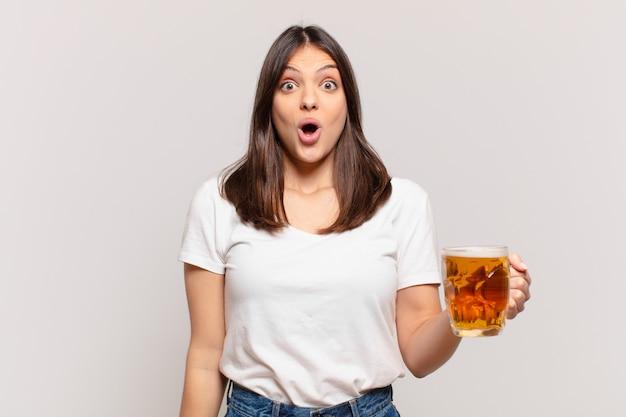 Młoda ładna kobieta przestraszona wypowiedzi i trzyma piwo