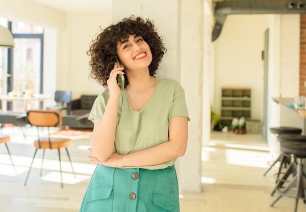 Młoda ładna kobieta przy użyciu swojego inteligentnego telefonu w nowym domu