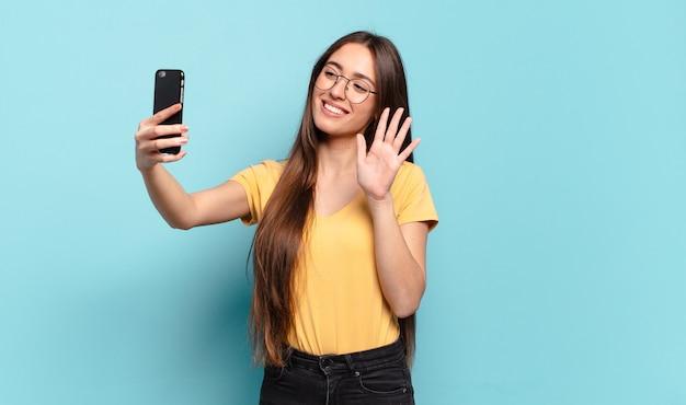 Młoda ładna kobieta przy użyciu swojego telefonu komórkowego.