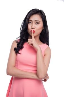 Młoda ładna kobieta robi cichy gest palcem na ustach