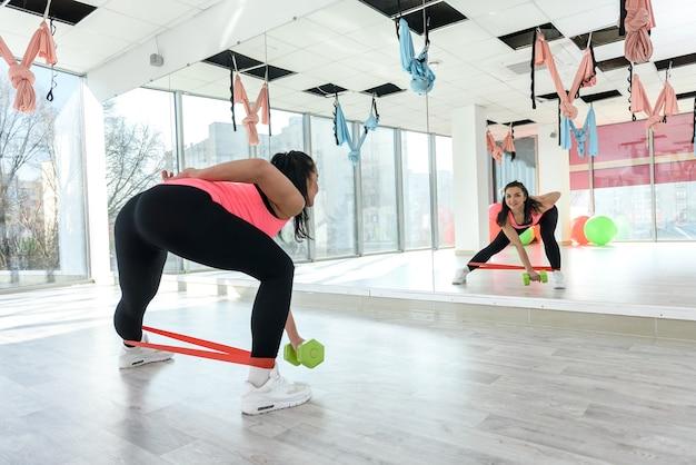Młoda ładna kobieta robi ćwiczenia trening siłowni bandaż elastyczny. trening zdrowotny