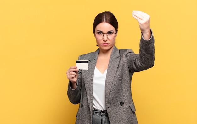 Młoda ładna kobieta robi gest kaprysu lub pieniędzy, każąc ci spłacić swoje długi!