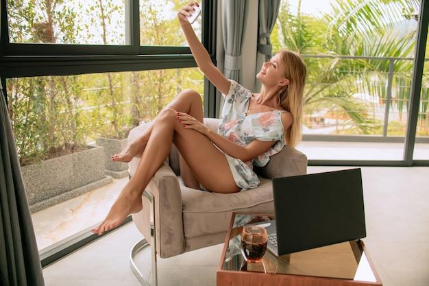 Młoda ładna kobieta robi selfie strzał na telefon komórkowy, praca przy biurku z komputera przenośnego laptopa. osiągnięcie stylu życia kariery biznesowej, koncepcja niezależna. duzi otwarte okno i natury tło
