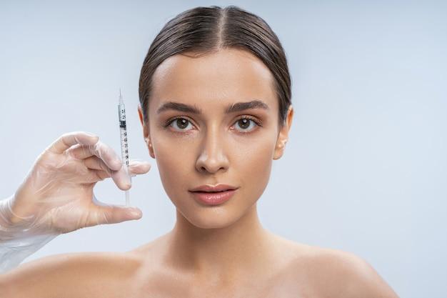 Młoda ładna kobieta robi zastrzyki z botoksu na twarz