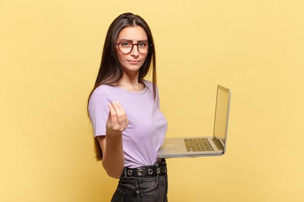 Młoda ładna kobieta robiąca gest capice lub pieniądze, mówiąca o spłacie długów!. koncepcja laptopa