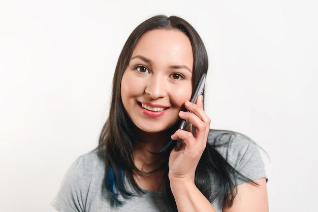 Młoda ładna kobieta rozmawia przez telefon i uśmiecha się