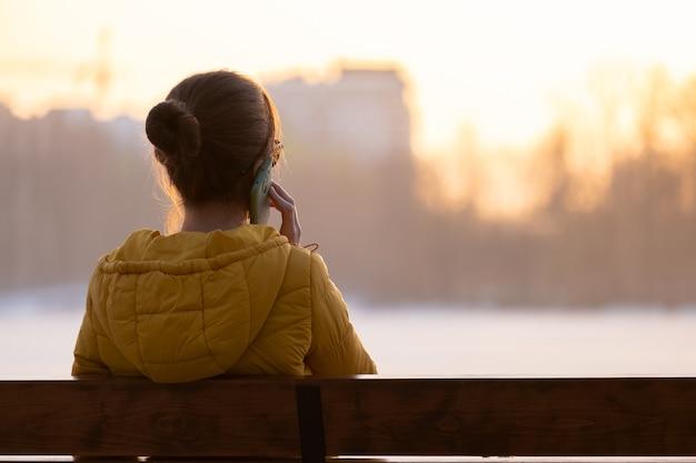 Młoda ładna kobieta siedzi na ławce wieczorem na zewnątrz swojego telefonu komórkowego.