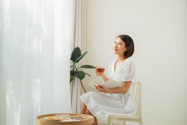 Młoda ładna kobieta siedzi przy oknie, pijąc herbatę i czytając książkę, lubi odpoczywać