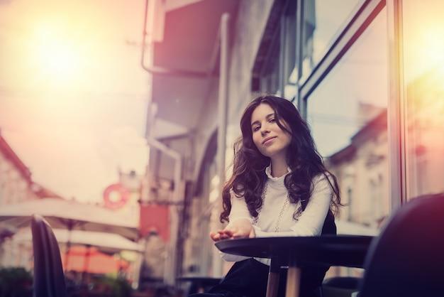 Młoda ładna kobieta siedzi w pobliżu kawiarni w centrum miasta i pozuje, ciesz się letnim stylem życia