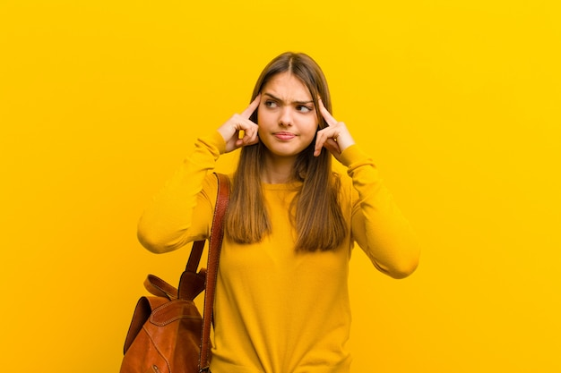 Młoda ładna kobieta, skoncentrowana i intensywnie zastanawiająca się nad pomysłem, wyobrażająca sobie rozwiązanie problemu lub problemu z pomarańczową ścianą