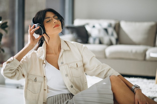 Młoda ładna kobieta słuchania muzyki na słuchawki bezprzewodowe
