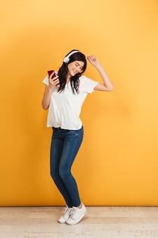 Młoda ładna kobieta słuchania muzyki trzymając telefon komórkowy.
