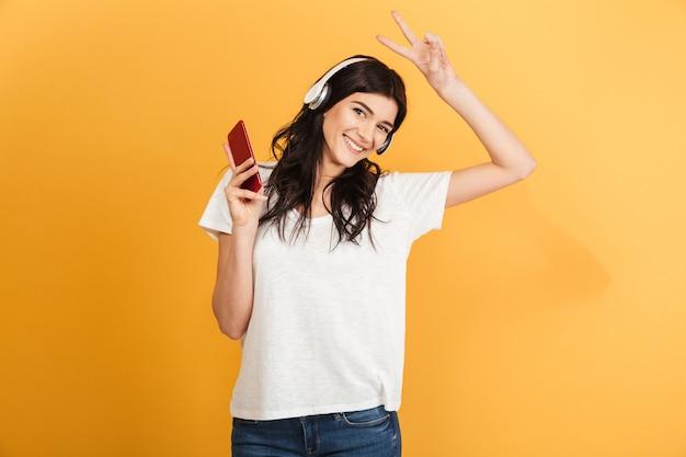 Młoda ładna kobieta słuchanie muzyki na czacie przez telefon komórkowy.