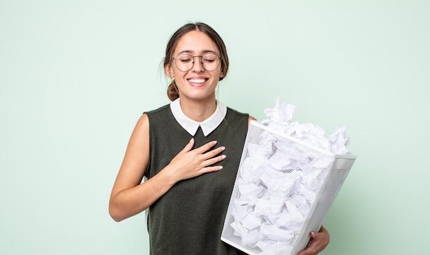 Młoda ładna kobieta śmiejąca się głośno z jakiegoś zabawnego żartu. koncepcja kosza z kulkami papierowymi