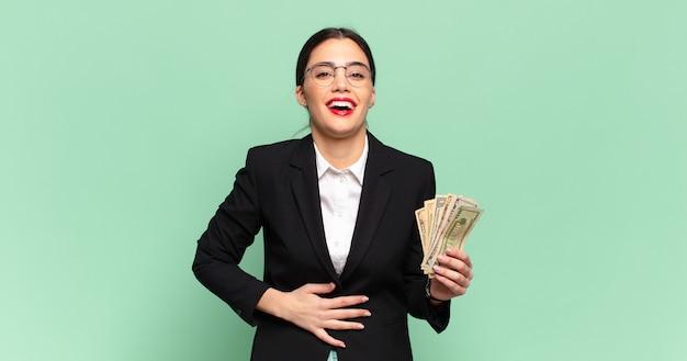 Młoda ładna kobieta śmiejąca się głośno z jakiegoś zabawnego żartu, szczęśliwa i wesoła, dobrze się bawiąca. koncepcja biznesu i banknotów