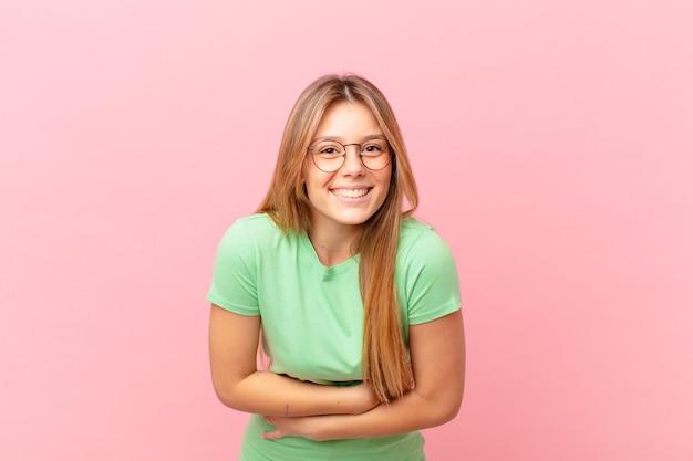 Młoda ładna kobieta śmiejąca się głośno z jakiegoś zabawnego żartu