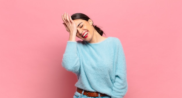 """Młoda ładna kobieta śmiejąca się i uderzająca w czoło, jak mówiąca """"oh""""! zapomniałem lub to był głupi błąd"""