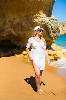 Młoda ładna kobieta spaceru na plaży latem