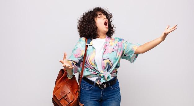Młoda ładna kobieta śpiewa w kolorowej koszuli