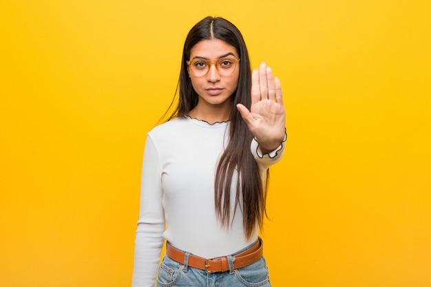 Młoda ładna kobieta stojąc z wyciągniętą ręką pokazując znak stop, zapobiegając ci