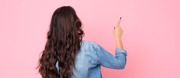 Młoda ładna kobieta stojąca i wskazująca na obiekt na przestrzeni kopii, widok z tyłu