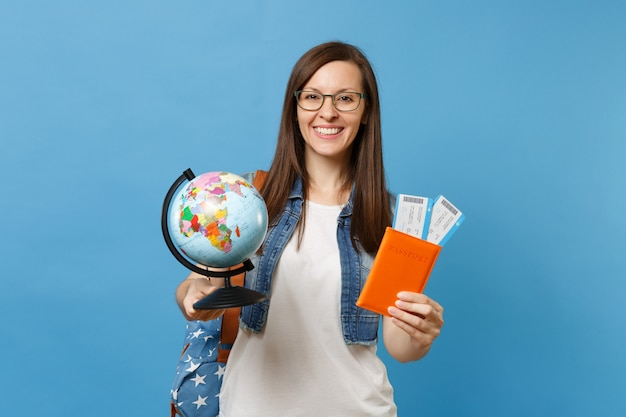 Młoda ładna kobieta studentka w okularach z plecakiem trzymając rękawiczki świata, paszport, bilety na pokład na białym tle na niebieskim tle. kształcenie na uczelniach wyższych za granicą. koncepcja lotu podróży lotniczych.